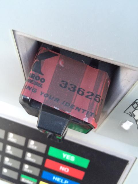 The security tape wrapped around this card reader at a Kangaroo station is intended to communicate that the credit card reader hasn't been altered.