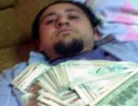 Ercan Findikoglu, posing with piles of cash.