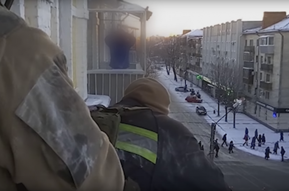 Kapkanov, in blue with his hands over his head, standing on his 4th-floor balcony. Image: npu.gov.ua