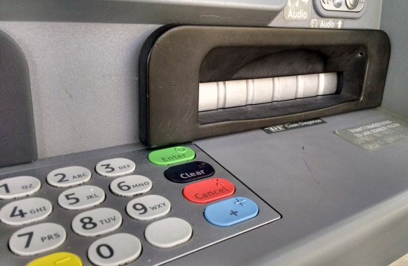 A closeup of the tiny pinhole that allows a mini spy camera embedded in the fake cash dispenser bezel to record customers entering their PINs.