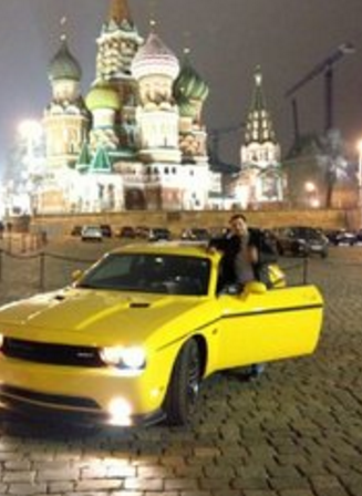 Seleznev posing with a sports car in Red Square. Image: DOJ.